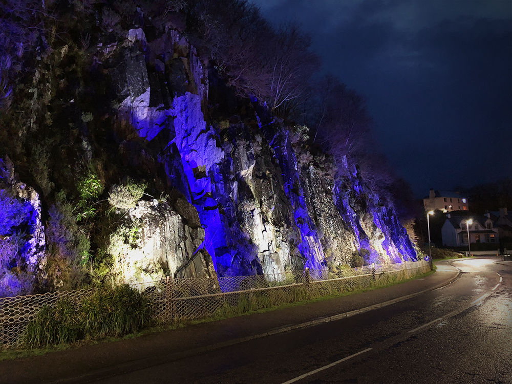 blue and white striped illumination on cliff face